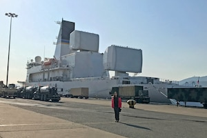 Maj. Christina Light, the Technical Operations Squadron Director of Operations with the Air Force Technical Applications Center, Patrick AFB, Fla., stands in front of the USNS Howard O. Lorenzen, a U.S. naval ship that hosts the $1.7 billion Cobra King radar platform.