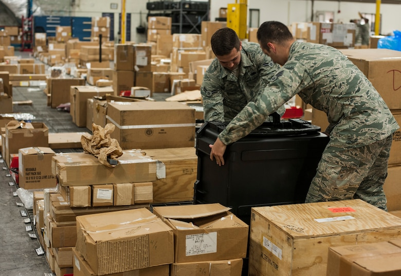 U.S. Air Force Airman 1st Class Justin Auger, a central storage technician, and Senior Airman Seth Soares, a flight service center technician, both assigned to the 6th Logistics Readiness Squadron, move a Pelican case at MacDill Air Force Base, Fla., April 11, 2018.