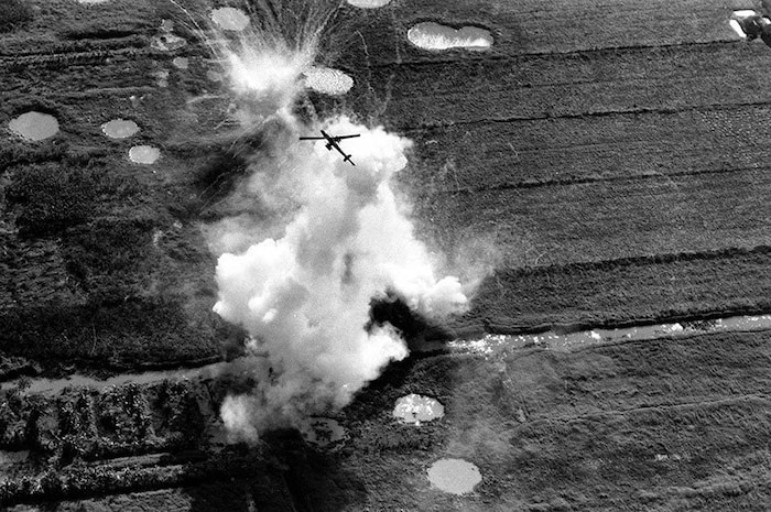 A UH-1E Gunship pulls out of a rocket and strafing attack on a Viet Cong position near Cao Lanh in the Mekong Delta, Jan. 22, 1969. Large craters caused by air and artillery strikes brought in on the area can be seen near the white explosion.