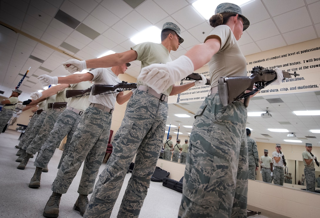 Airmen watch themselves perform a rifle volley in the mirror during an honor guard training session April 2, 2018, at Eglin Air Force Base, Fla. The Air Force Honor Guard mobile training team visited the base to provide a 10-day standardized training course to 31 local honor guard Airmen. The goal is to ensure all honor guard units perform the required ceremonial procedures the same way throughout the Air Force. (U.S. Air Force photo by Samuel King Jr.)