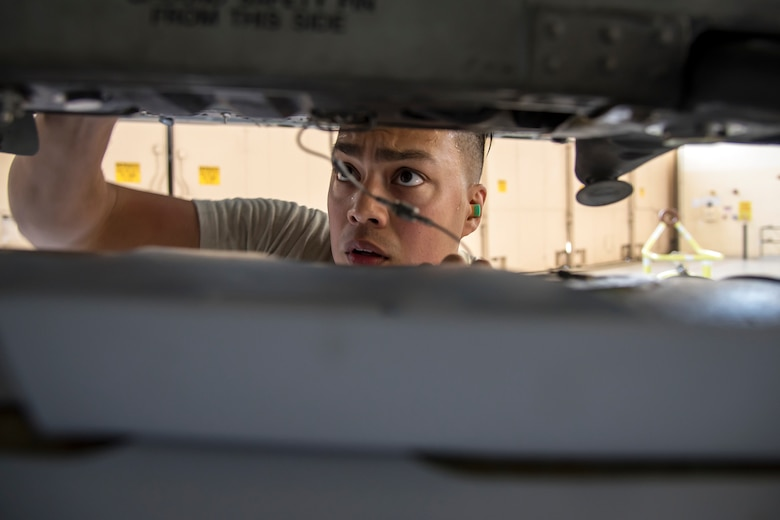 Staff Sgt. Jorge Galvez, 74th Aircraft Maintenance Unit (AMU) weapons load crew team chief, inspects the alignment of an inert MK-84 general purpose bomb during a weapons-load competition, April 6, 2018, at Moody Air Force Base, Ga. During the load portion of the competition Airmen from the 74th and 75th AMU were assessed on their ability to quickly and efficiently load munitions onto an A-10. They were also judged on dress and appearance and a written test based on munitions knowledge. (U.S. Air Force photo by Airman Eugene Oliver)