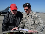 Father and son, one in Air Force uniform, look at a maintenance manual.