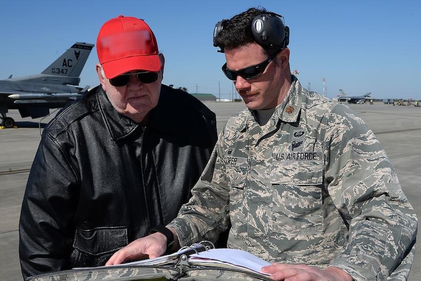 Two men look over some paperwork at an airfield.