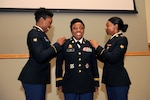 Army Spc. Nia Davis (left) and Army Spc. Raven Lee (right) affix the rank insignia to Army Lt. Col. Latrina Lee's (center) uniform during her promotion ceremony April 6. The two specialists are the nieces of Lt. Col. Lee, DLA Troop Support chief of current operations.