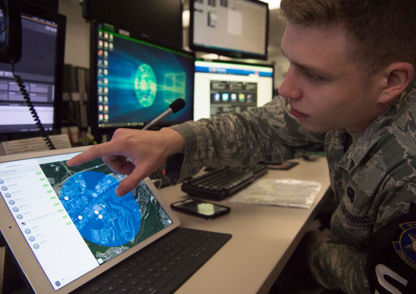 U.S. Air Force Senior Airman Zachary Robertson, 569th United States Forces Police Squadron desk controller, uses a tablet and satellite tracking application to perform the same function of a much more expensive system on Vogelweh Military Complex, Germany, March 9, 2018. The innovation is saving the 569th USFPS an estimated $286,200 and 369 man hours per fiscal year. (U.S. Air Force photo by Senior Airman Elizabeth Baker)