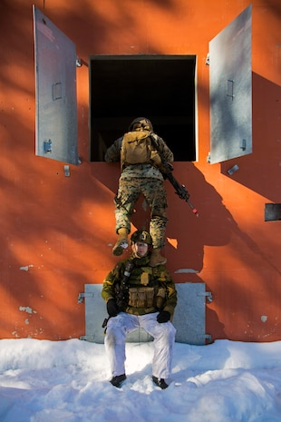 A Marine with Marine Rotational Force-Europe 18.1 climbs over a Norwegian soldier during close-quarters combat training at Leksdal Skytefelt Training Complex, Norway, March 27, 2018. The law enforcement Marines integrated with Norwegian Home Guard 12 to learn new breaching and clearing tactics. The event is one of many training evolutions the Marines plan to execute with their NATO Allies, enhancing strategic cooperation and partnership between the U.S. and Norway.