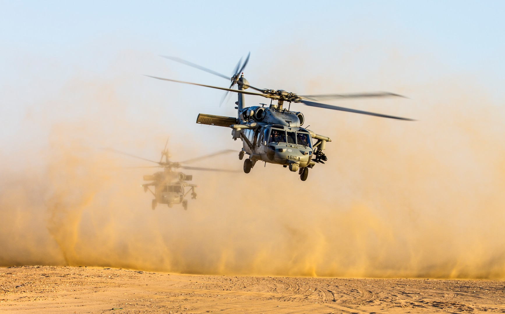 Two Navy MH-60S Sea Hawk helicopters from USS George H.W. Bush take off during joint fire exercise with Army AH-64 Apaches from 3rd Battalion, 159th Attack Reconnaissance Battalion, 42nd Combat Aviation Brigade, and Air Force joint terminal attack controllers from 82nd Expeditionary Air Operations Squadron, on July 8, 2014, near Camp Buehring, Kuwait (New York Army National Guard/Harley Jelis)