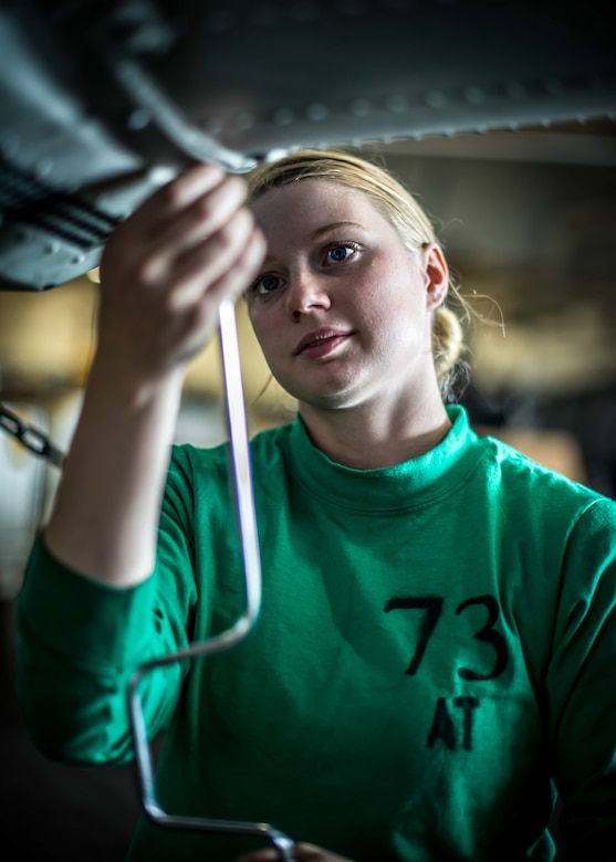 Aviation Electronics Technician assigned to Battlecats of Helicopter Maritime Strike Squadron 73 conducts maintenance on MH-60R Seahawk in hangar bay of USS Theodore Roosevelt, Pacific Ocean, April 24, 2017 (U.S. Navy/Bill Sanders)