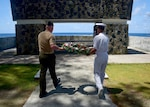 A Marine and a sailor lay a wreath.