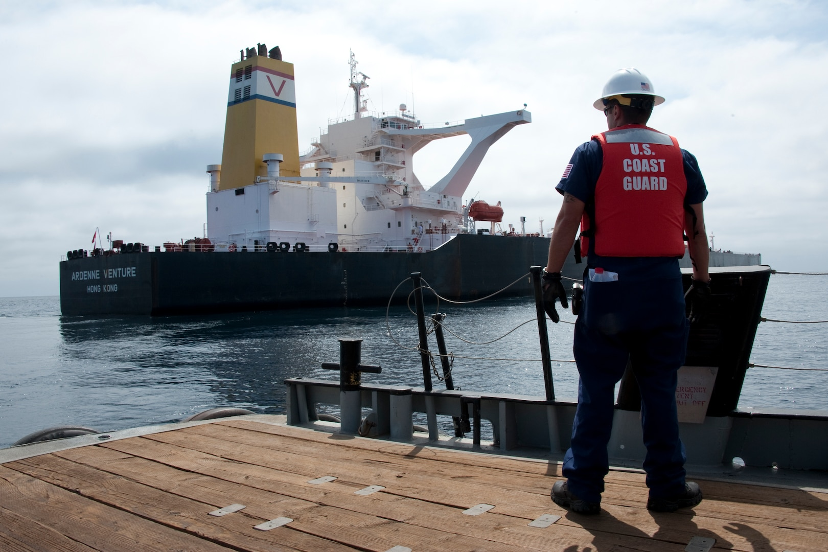 U.S. Coastguardman watches as crew boat departs from Ardenne Venture after annual exam to ensure it complies with U.S. and international regulations prior to operating in U.S. waters and ports, San Diego, California, August 3, 2012 (U.S. Coast Guard/Henry G. Dunphy)