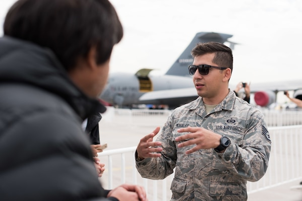 U.S. Air Force Staff Sergeant Humberto Morales, 56th Operations Support Squadron Aircrew Flight Equipment Journeyman, Luke Air Force Base, Arizona, participates in a discussion with members of the Chilean public during the FIDAE 2018 international airshow in Santiago, Chile, April 6, 2018.  U.S. airmen participated in a variety of activities during the air show, including subject matter exchanges with the Chilean Air Force, aerial demonstrations, and interaction with the local community.  (U.S. Air Force photo by Staff Sgt. Danny Rangel)