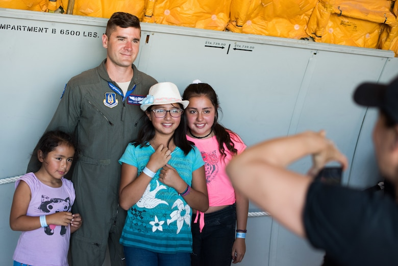 U.S. Air Force Staff Sergeant Luke Findley, 79th Air Refueling Squadron Boom Operator, Travis Air Force Base, California, poses for a photograph with members of the Chilean public during the FIDAE 2018 international airshow in Santiago, Chile, April 8, 2018.  U.S. airmen participated in a variety of activities during the air show, including subject matter exchanges with the Chilean Air Force, aerial demonstrations, and interaction with the local community.  (U.S. Air Force photo by Staff Sgt. Danny Rangel)