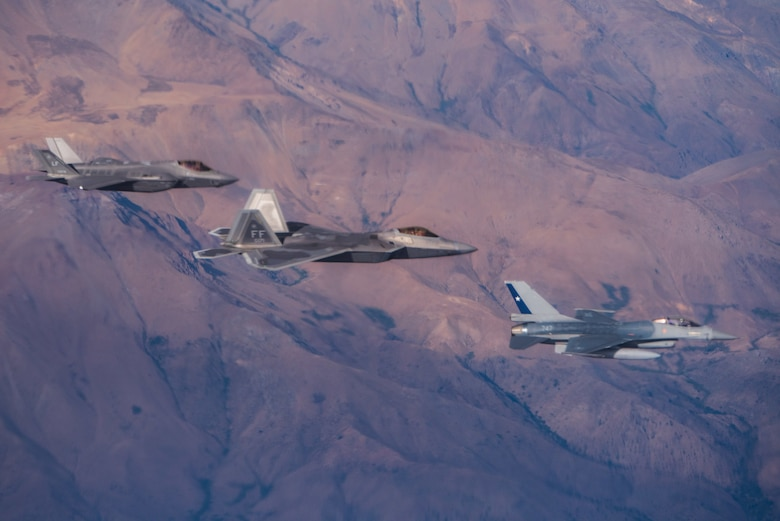 A U.S. Air Force F-35 Lightning II, F-22 Raptor and Chilean Air Force F-16 fly together during a formation flight before their arrival in Santiago, Chile for FIDAE 2018, March 30, 2018.  U.S. airmen participated in a variety of activities during the air show, including subject matter exchanges with the Chilean Air Force, aerial demonstrations, and interaction with the local community.  (U.S. Air Force photo by Staff Sgt. Danny Rangel)