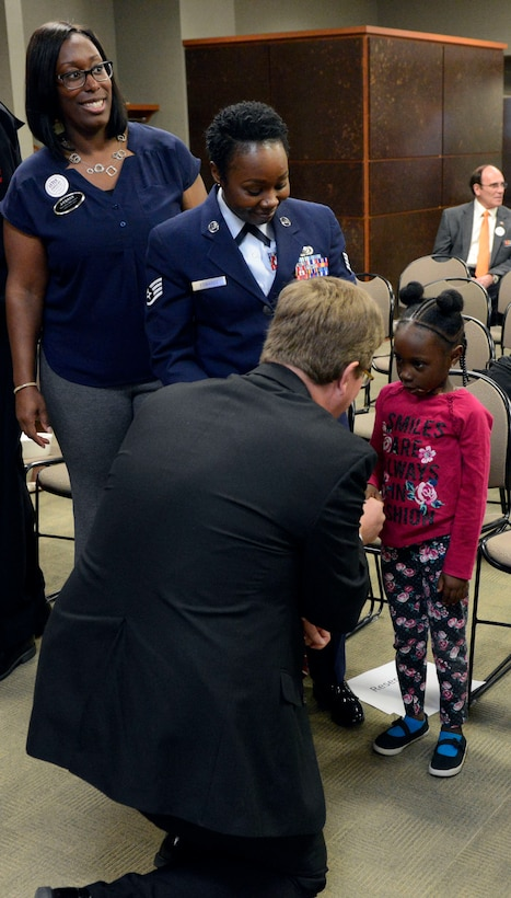 Two black women and a small black girl shake hands with a white man.