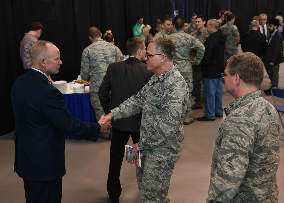 Brig. Gen. Michael Schmidt, left, greets Col. Richard McDermott, 66th Air Base Group Staff Judge Advocate, center, following his assumption of leadership of the Command, Control, Communications, Intelligence and Networks directorate at Hanscom Air Force Base, Mass., April 13, 2018 at the Hanscom Aero Club hangar. (U.S. Air Force Photo by Linda LaBonte Britt)