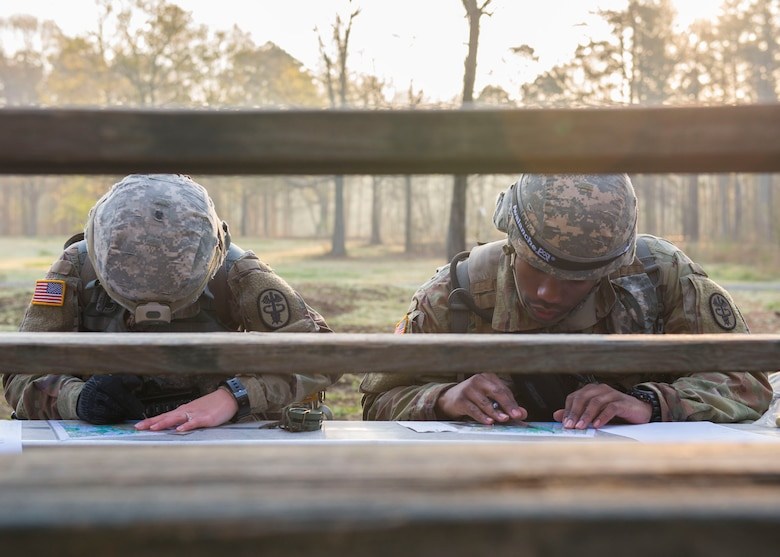 U.S. Army Spc. Natasha Shaw, Medical Department Activity optical lab specialist, and U.S. Army Sgt. Dequan Davis, MEDDAC patient administrator, study maps in Fort Eustis' Training Area 23 at Joint Base Langley-Eustis, Virginia., April 11, 2018. The Soldiers were tasked with locating four designated points using only a map and compass in a land navigation exercise. (U.S. Air Force photo by Airman 1st Class Monica Roybal)