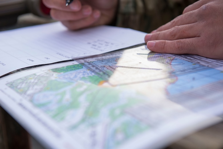 A U.S. Army Soldier plans a route for a land navigation exercise in Fort Eustis' Training Area 23 at Joint Base Langley-Eustis, Virginia., April 11, 2018. Soldiers used a map protractor to plot coordinates then used a compass to locate each point. (U.S. Air Force photo by Airman 1st Class Monica Roybal)