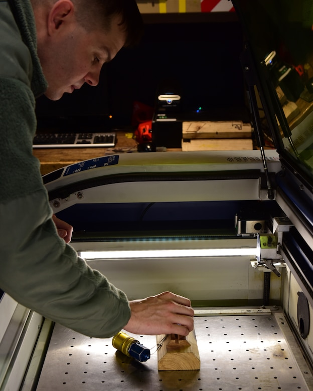 U.S. Air Force Staff Sgt. Randell White, a mobility support technician assigned to the 509th Aircraft Maintenance Squadron, places a piece of equipment in the Epilog Laser Fusion M2 to be engraved with a label at Whiteman Air Force Base, Mo., April 10, 2018. The Fusion M2 model is a dual-source laser system that allows the Airmen to perform both metal marking applications and CO2 laser applications from the same system, in the same job. (U.S. Air Force photo by Staff Sgt. Danielle Quilla)