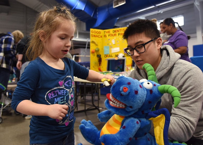 Maggie Kaufhold, 5-year-old, shows Senior Airman Kevin Yi, 319th Medical Operations Squadron dental assistant, how to properly brush teeth on a stuffed animal Apr. 10, 2018, on Grand Forks Air Force Base, N.D. Several agencies joined together for the Beautiful Child event, an annual children's activity fair.(U.S. Air Force photo by Staff Sgt. Desiree Economides)