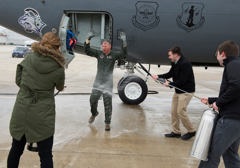 The children of Col. James P. Ryan, retired 157th Air Refueling Wing commander, spray him with champagne and fire extinguishers, part of the aviator's tradition known as the fini-flight, on Feb. 23, 2018 at Pease Air National Guard Base, N.H. Ryan flew his last flight in a KC-135 Stratotanker less than two months before his retirement. (N.H. Air National Guard photo by Staff Sgt. Kayla White)