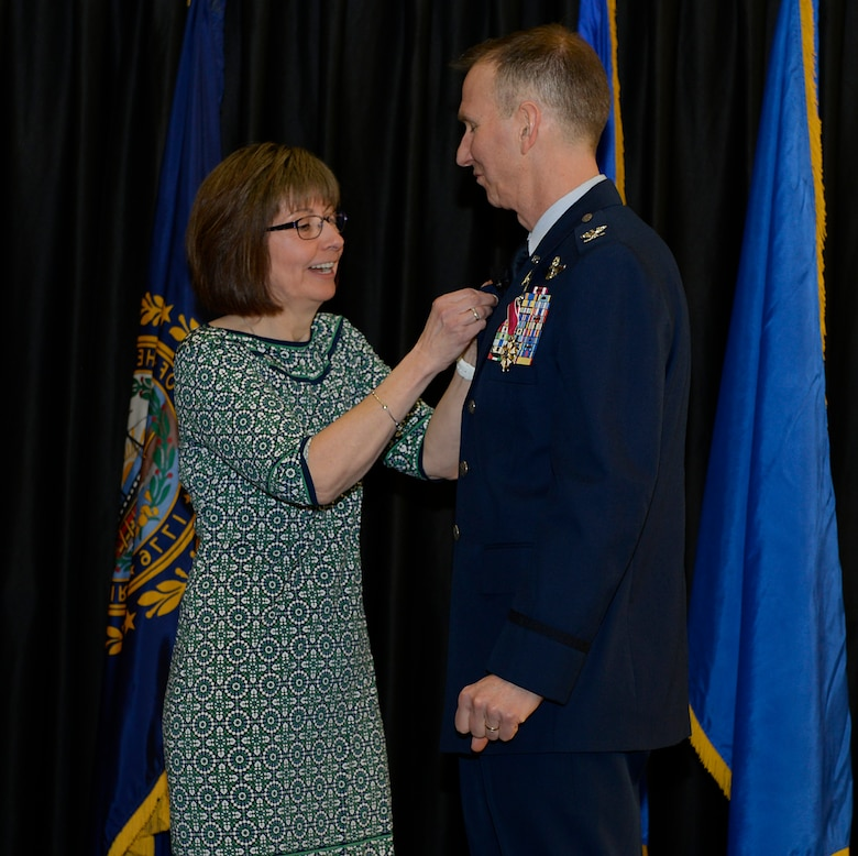 Mary Ellen, wife of Col. James P. Ryan, retired, 157th Air Refueling Wing commander, pins his retirement pin to his jacket on April 07, 2018 at Pease Air National Guard Base, N.H. Ryan retired after more than 30 years of service. (N.H. Air National Guard photo by Airman 1st Class Victoria Nelson)