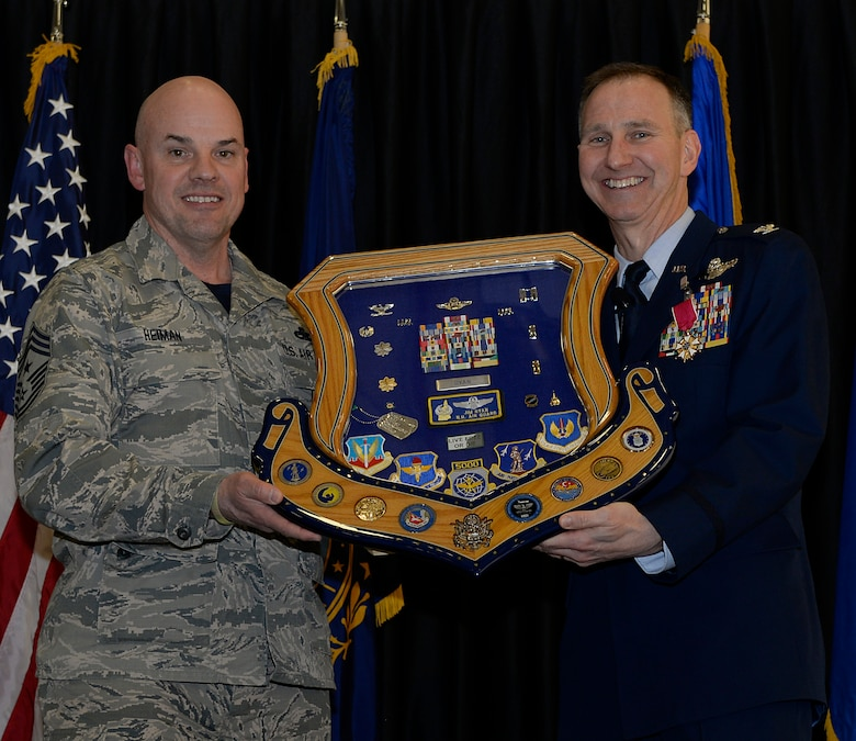 Col. James P. Ryan, retired 157th Air Refueling Wing commander, receives his shadow box from Command Chief Master Sgt. Matthew S. Heiman, the 157th ARW command chief, on April 07, 2018 at Pease Air National Guard Base, N.H. The shadow box serves as a visual representation of Ryan's career, after more than 30 years of service. (N.H. Air National Guard photo by Airman 1st Class Victoria Nelson)
