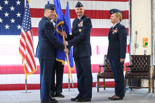 Col. Jon A. Eberlan (center), 75th Air Base Wing commander, accepts the wing guidon from Lt. Gen. Lee K. Levy II, Air Force Sustainment Center commander, during a 75th ABW change of command ceremony April 13, 2018, at Hill Air Force Base, Utah. Watching is Col. Jennifer Hammerstedt, formerly the 75th ABW commander. (U.S. Air Force photo by Cynthia Griggs)