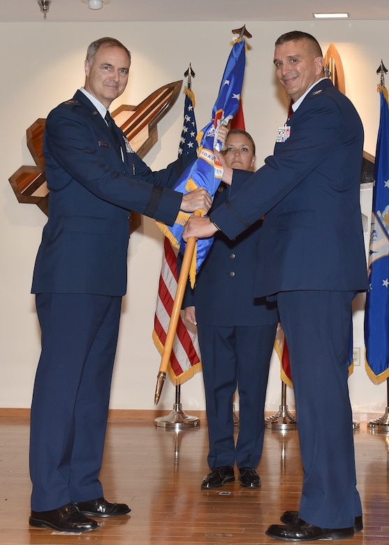 Col. Michael Valle, 101st Air and Space Operations Group commander, takes the ceremonial flag from Lt. Gen. R. Scott Williams, Continental U.S. NORAD Region – First Air Force (Air Forces Northern) commander, during the 601st Air Operations Center change of command ceremony at Tyndall Air Force Base, Florida on April 13, 2018.