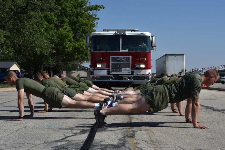 Marines from the Marine Detachment on Goodfellow hold a push-up position before pulling a firetruck during Sports Day at the Mathis Fitness Center on Goodfellow Air Force Base, Texas, April 13, 2018. Teams worked together to pull the firetruck across the line as quickly as possible.