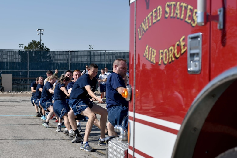 Members from the 35th Training Squadron work together to pull a firetruck during Sports Day at the Mathis Fitness Center on Goodfellow Air Force Base, Texas, April 13, 2018. An average firetruck may weigh 19 Tons, or 41,887 pounds.