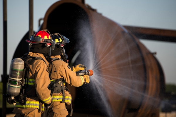 Firefighters from Joint Base San Antonio-Randolph prepare a fire hose before entering a mockup aircraft April 11, 2018 at the Camp Talon fire training grounds on JBSA-Randolph. The training offers firefighters the opportunity to train with live fire to get as close to a real-life scenario as possible. (U.S. Air Force photo by Senior Airman Gwendalyn Smith)