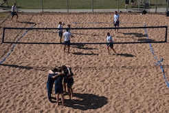Airmen huddle before beginning a sand volleyball match during the Sports Day at Mathis Fitness Center on Goodfellow Air Force Base, Texas, April 13, 2018. Many different units from Goodfellow competed, but the 315th Training Squadron took first place in this category.