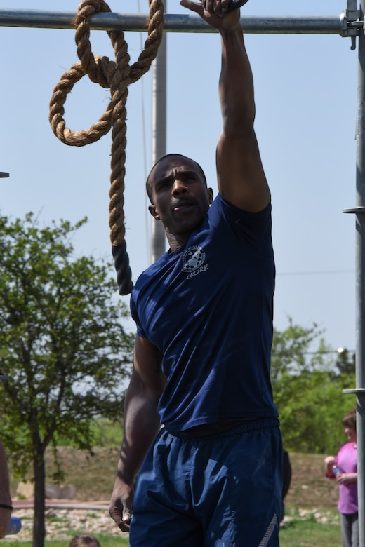 """Master Sgt. Jamaal Chesney swings through the Alpha Warrior """"Battle Rig"""" during Sports Day on Goodfellow Air Force Base, Texas, April 13, 2018. Chesney was later awarded 1st place for the Alpha Warrior competition."""