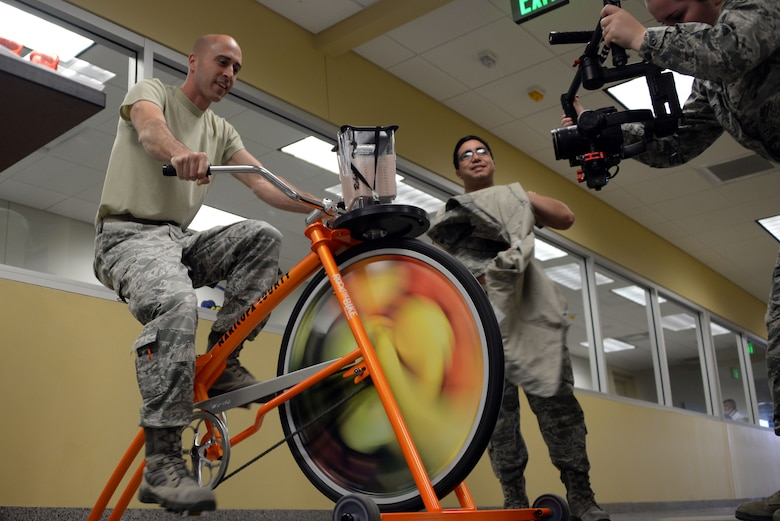 Airmen from the 62nd Aircraft Maintenance Unit participate in blending their own smoothie on a smoothie bike presented by the 56th Medical Group health promotions at Luke Air Force Base, Ariz., April 5, 2018.  The 56th MDG is celebrating National Nutrition Month by inspiring Thunderbolts to eat healthier and promoting overall wellness. (U.S. Air Force photo by Senior Airman Devante Williams)