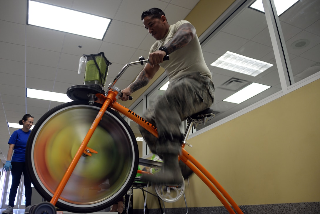 "An Airman from the 62nd Aircraft Maintenance Unit powers a blender with a stationary bike during 56th Medical Group health promotion at Luke Air Force Base, Ariz., April 5, 2018. The 56th MDG is celebrating National Nutrition Month, which is themed ""Go Further with Food."" The campaign focuses on the importance of making informed food choices and developing sound eating and exercising habits. (U.S. Air Force photo by Senior Airman Devante Williams)"