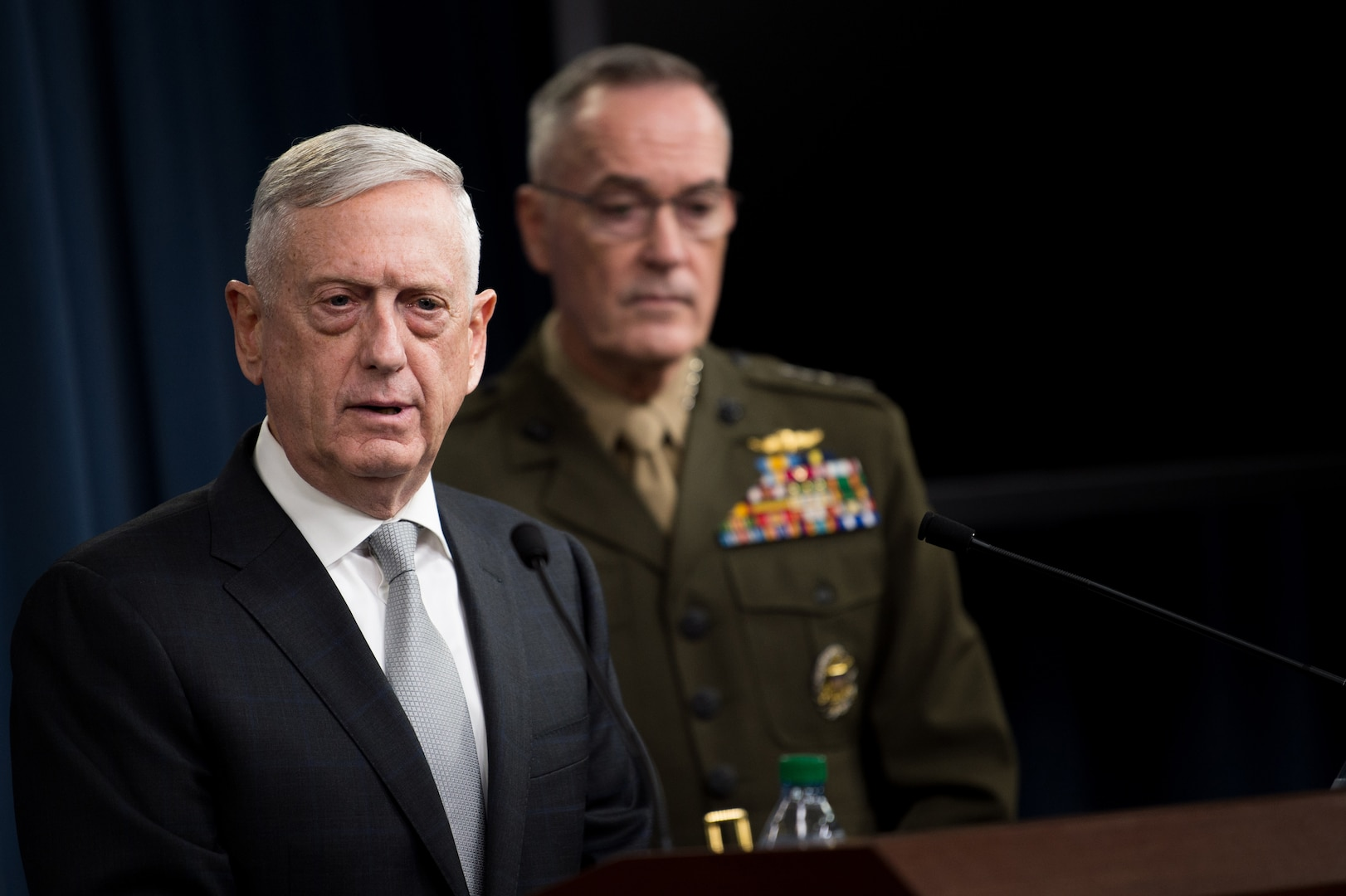Defense Secretary James N. Mattis speaks at a lectern while Marine Corps Gen. Joe Dunford stands by.