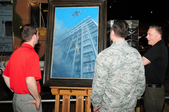 Mike Rowland, Museum of Aviation curator, Col. John Heck, Air Force Reserve Command Historian's office and Darby Perrin, a boom operator assigned to the 507th Air Refueling Wing, Tinker Air Force Base, Oklahoma, speak during a showing of Perrin's latest painting at the Museum of Aviation in Warner Robins, Ga., April 13, 2018. Perrin, the artist of the painting created the work depicting a helicopter rescue at the MGM Grand Hotel in Las Vegas. The work shows a disaster that killed 85 people and injured more than 700 on November 21, 1980. (U.S. Air Force photo by Staff Sgt. Ciara Gosier)