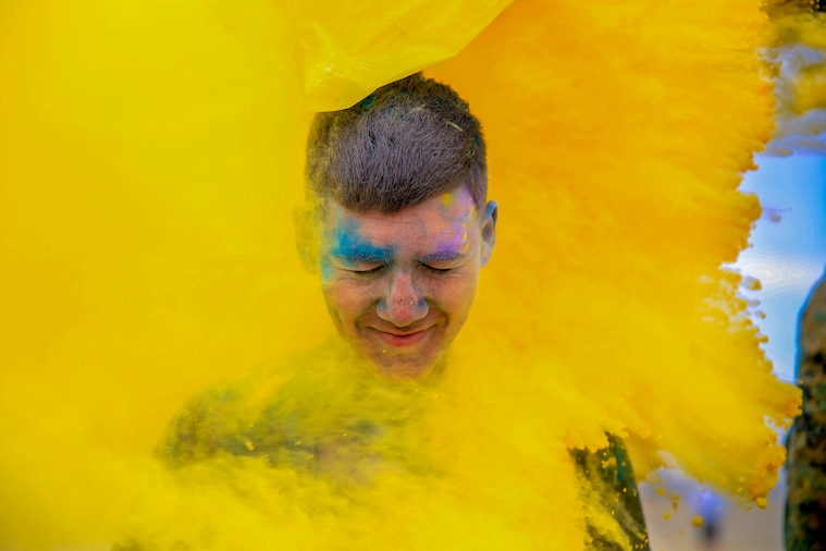 A Marine's grinning face, smeared with blue and purple powder, emerges from the center of a think cloud of yellow powder.