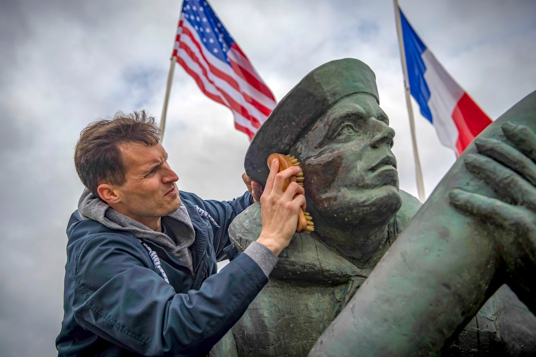A sailor uses a brush to scrub the face of a statue outside, with a U.S. flag and a French flag in the background.