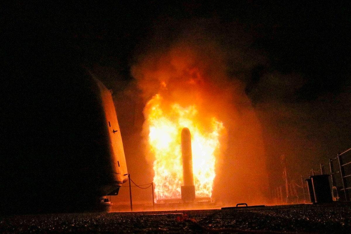 A missile surrounded by flames launches from a ship at night.