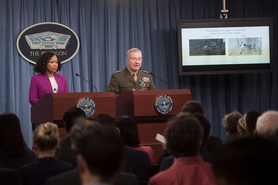 A civilian and a Marine stand at lecterns and brief reporters.