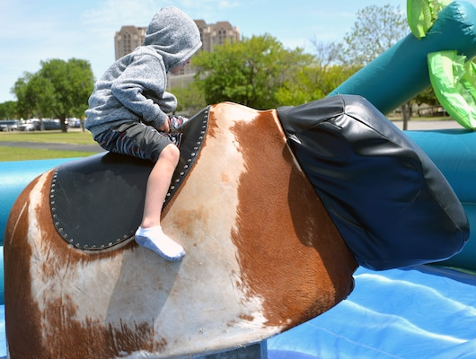 A young would-be bull rider clings on for dear life on a mechanical bull during the annual Cowboys and Heroes event held at MacArthur Parade Field at Joint Base San Antonio-Fort Sam Houston April 14.