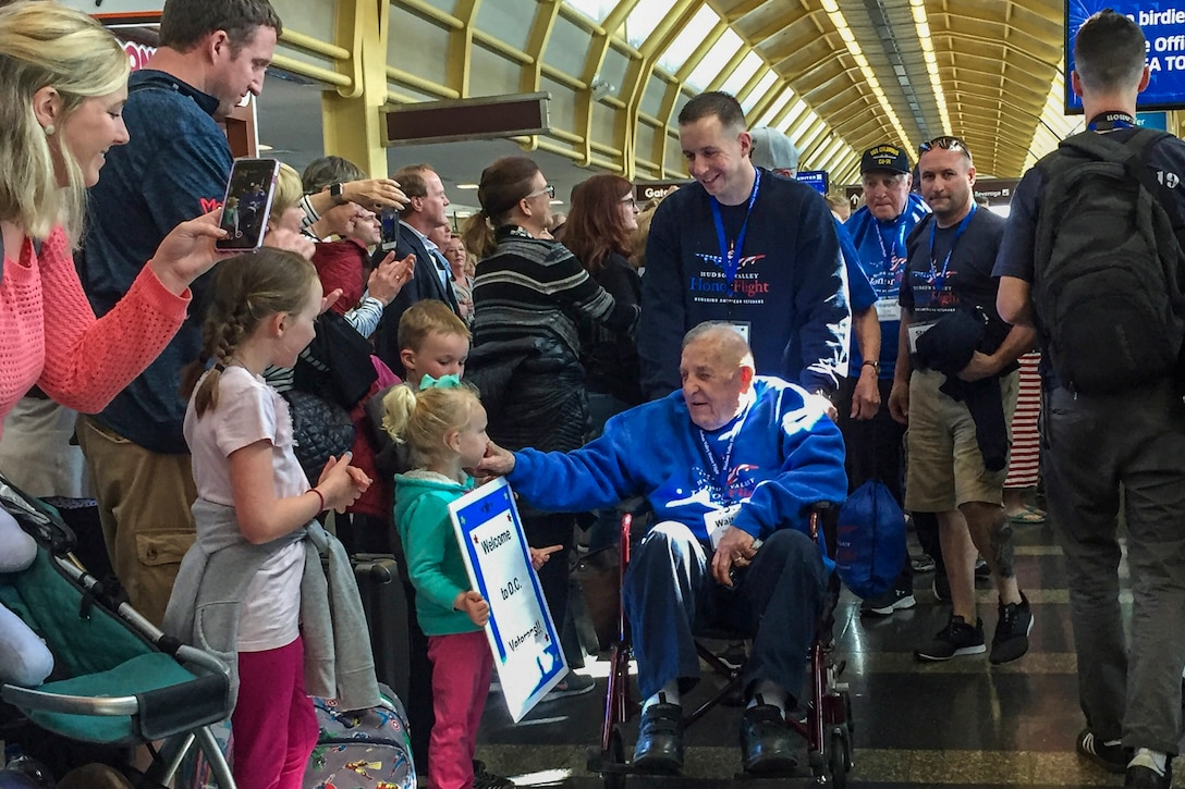 An elderly man in a wheelchair exchanges greetings with well-wishers gathered in an airport terminal.