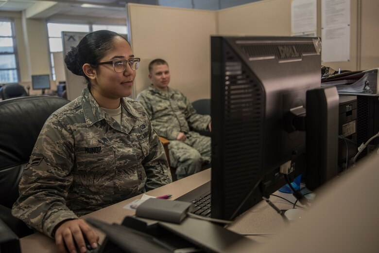 U.S. Air Force Airman 1st Class Leann Munoz, 18th Force Support Squadron customer service technician, creates a new common access card for Tech. Sgt. Michael Evans, 718th Aircraft Maintenance Squadron NCOIC of computer electronic warfare, Mar. 29, 2018, at Kadena Air Base, Japan. The 18th FSS Military Personnel Section implemented a new process that enables customers to file for a dependent identification card from their cell phones or personal emails. The new system saves customers time and enables the MPS to complete more tasks. (U.S. Air Force photo by Staff Sgt. Micaiah Anthony)