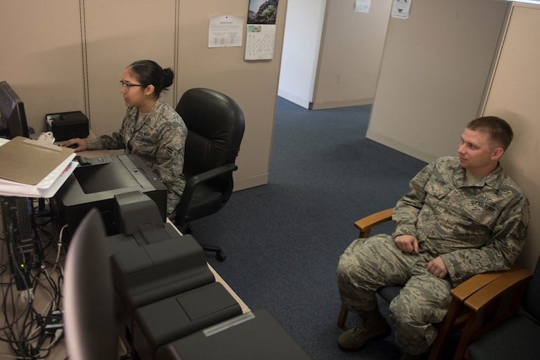 U.S. Air Force Airman 1st Class Leann Munoz, 18th Force Support Squadron customer service technician, creates a new common access card for Tech. Sgt. Michael Evans, 718th Aircraft Maintenance Squadron NCOIC of computer electronic warfare, Mar. 29, 2018, at Kadena Air Base, Japan. The 18th FSS Military Personnel Section implemented a new process that enables customers to file for a dependent identification card from their cell phones or personal emails. Kadena is the 5th base to implement this new process. (U.S. Air Force photo by Staff Sgt. Micaiah Anthony)