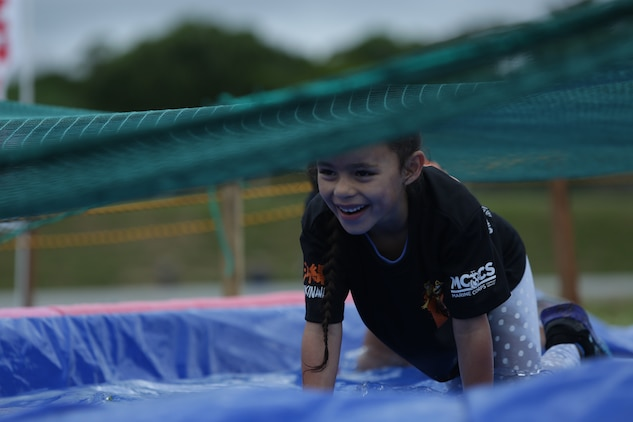 CAMP HANSEN, OKINAWA, Japan – A child crawls though a pool of water during the children's 1k at the 2018 Camp Hansen World Famous Mud Run April 15 aboard Camp Hansen, Okinawa, Japan.