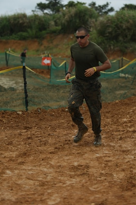 CAMP HANSEN, OKINAWA, Japan – 1st Lt. Francisco Urbina runs through the mud obstacles during the 2018 Camp Hansen World Famous Mud Run April 15 aboard Camp Hansen, Okinawa, Japan.