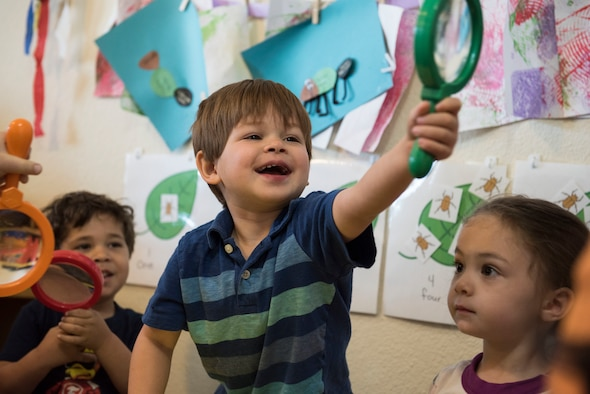 A child plays with a magnifying glass during an activity at a Family Child Care at Shaw Air Force Base, S.C., April 12, 2018.