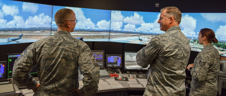SSgt. Iiae Hess demonstrates the flight simulator for Col. Eaglin and Chief Daniels.