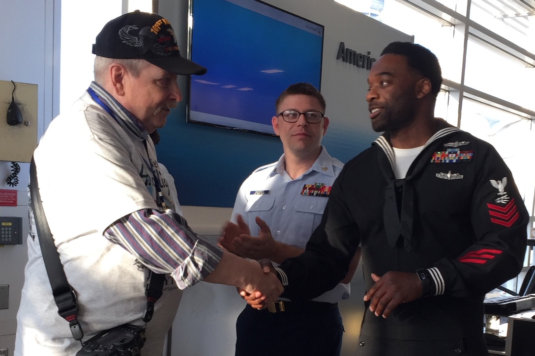 A sailor shakes hands with a veteran as he arrives at an airport.